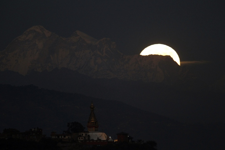 The moon rises behind the Dorje Lakpa Mountain as Swayambhunath stupa is seen in forground in Kathmandu, Nepal, Monday, Nov. 14, 2016. The brightest moon in almost 69 years lights up the sky this week in a treat for star watchers around the globe. The phenomenon known as the supermoon will reach its most luminescent in North America before dawn on Monday. (AP Photo/Niranjan Shrestha)